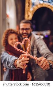 Couple holding Heart Shape Candy Cane