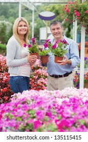 Couple holding purple plants in garden centre and smiling
