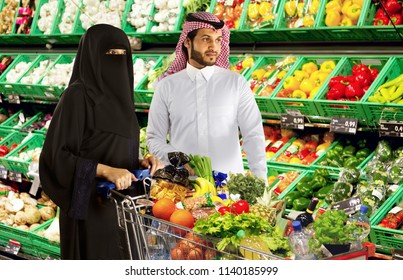 A couple holding push kart shopping together for vegetables and fruits in super market mall in Saudi Arabia Gulf Middle East