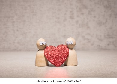 Couple holding red heart. Wooden figures with cute and funny symbol of love. Concept of romantic feelings, dating insecurity and valentine celebration.