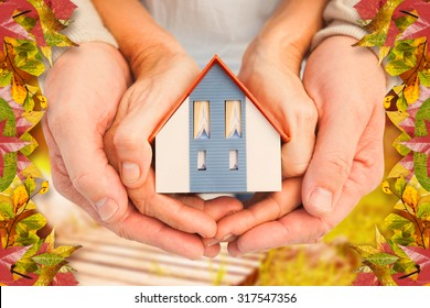 Couple holding small model house in hands against autumn scene