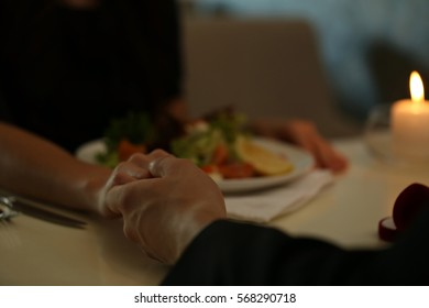 Couple holding their hands in restaurant