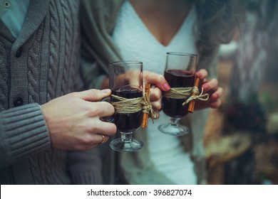 Couple holding wine glasses with mulled wine