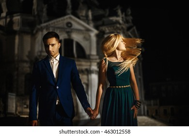 Couple holds each other hand in front of building
