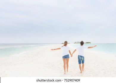 Couple holds each other for hands and walks on the white spit of island. Man and woman walk on the beach.