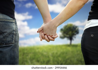 A couple holds hands in a park
