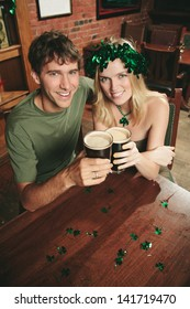 Couple holds up a pint of stout in a St. Patrick's Day themed pub.