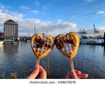 Couple hält zwei herzförmige Waffeln auf Holzstöcken mit Pulver für Zucker und Schokolade auf unscharfem Hintergrund der Elbe und des Hamburger Hafens