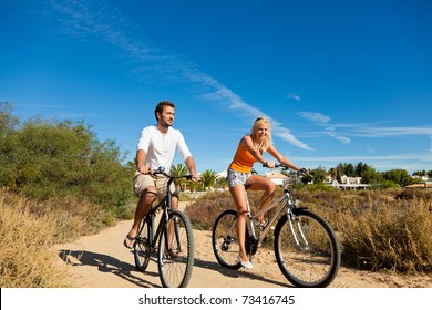 Couple in holidays cycling under a blue sky in the dunes on a beach