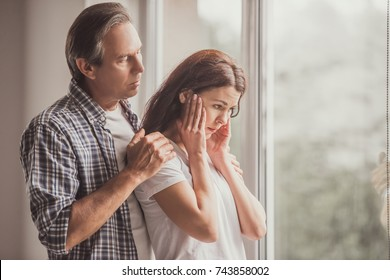 Couple at home. Handsome mature man is calming his upset wife while both are standing near the window