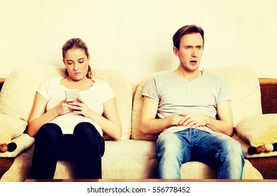 Couple at home, man watching tv woman using smartphone