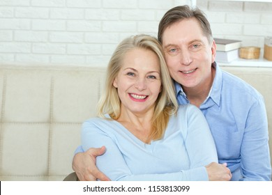 Couple at home on the couch talking and smiling. Closeup