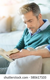 Couple at home reading book, man in foreground