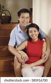 Couple at home, sitting on stairs