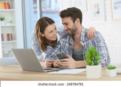 Couple at home using smartphone in front of laptop