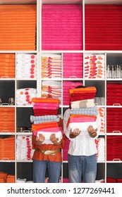 Couple homeware shopping with piles of towels in shop in front of stocked shelves
