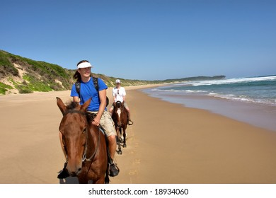 Couple of horse riders on beach. Shot in Sodwana Bay Nature Reserve, KwaZulu-Natal province, Southern Mozambique area, South Africa.