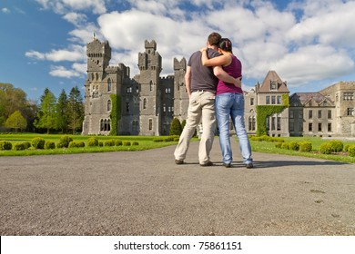 Couple in hug looking to the idyllic Ashford castle - Ireland