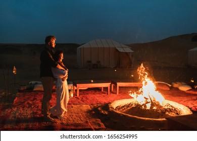 Verliebt in große Lagerfeuer umarmen. Romantische Nacht im Glamping Wüstenlager in Sahara, Marokko. Flitterwochen.