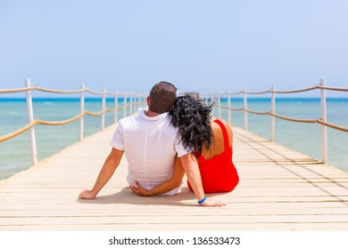 Couple in hug resting on the pier of Red Sea, Egypt