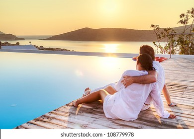 Couple in hug watching sunrise together in Greece