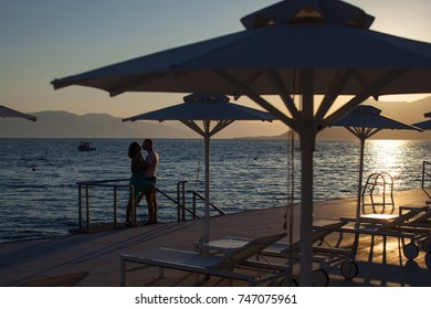 Couple in hug watching sunrise together in Greece. Romantic couple on the beach. Happy romantic couple on the beach at sunset. Young lovers on vacation. Happy day. Holidays. Romantic lovers. Sensual.