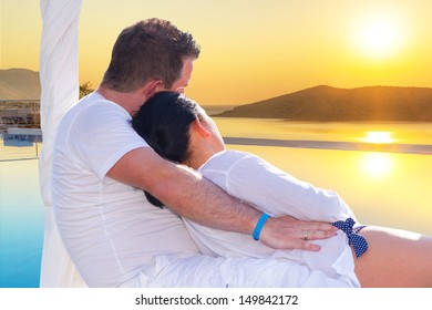 Couple in hug watching together sunrise in Greece