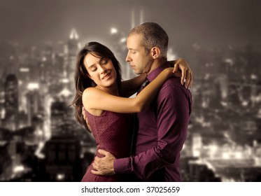 couple hugging against a night scene of city