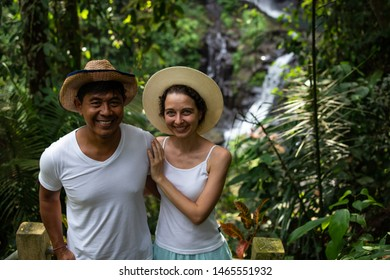 Couple hugging and enjoying waterfall scenery in tropical rainforest. Young mixed race couple on vacation in Asia. Romantic relationship. Love story. Couple in hats. Pengibul waterfall, Ubud, Bali.