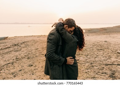 Couple hugging and kissing by the water
