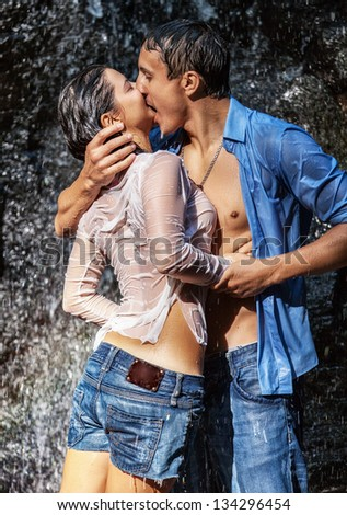 couple hugging kissing under waterfall stock photo edit now