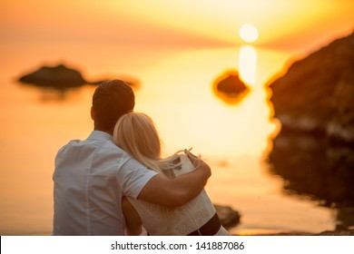 couple hugging on the beach on sunrise
