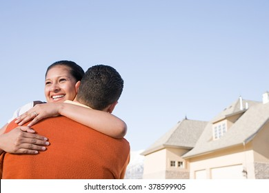 A couple hugging outside their new home