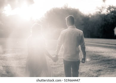 couple hugging in the rays of sunset light in the park in the summer