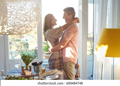 Couple hugging sharing a moment before their guests arrives for a dinner party