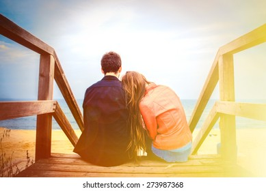 Couple is hugging sitting on the wooden bridge on the beach