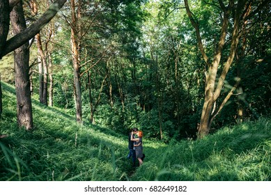 couple hugging while standing in the middle of the forest meadow