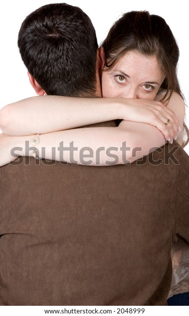 couple hugging - woman is looking intensely at the camera over his shoulder - white background