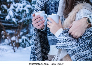 Couple hugs and holds cups of coffee with marshmallow