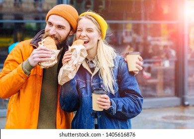 Couple is hungry and eating a burger croissants at lunch time in the city street outdoor. Beard man and blond woman holding cups and drinking coffee to go.Family is looking at camera and smiling