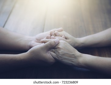 Couple of husband and wife are holding hands and pray together  on wooden table  with the light from above with  copy space for your text