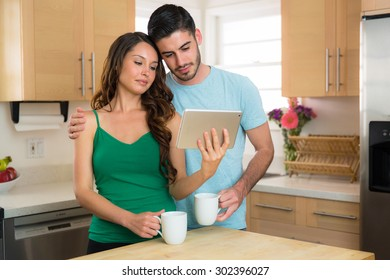 Couple husband wife sharing a tablet watching a movie video online with coffee in the morning nice sunny day
