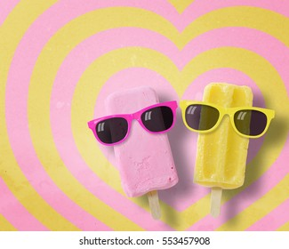 Couple ice cream stick wearing sunglasses on hearts pattern pink and yellow background with copy space.,Pastel tone.