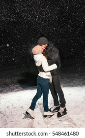 Couple ice skating outdoors on a pond on night