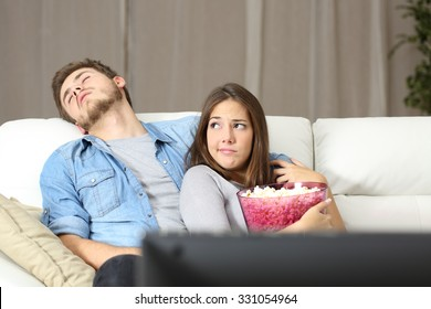 Couple incompatibility problems watching tv sitting on a couch at home
