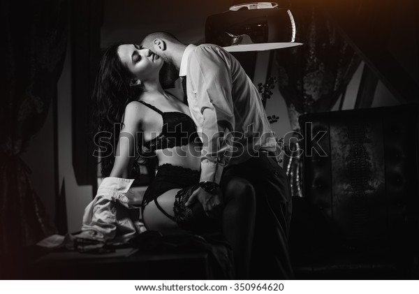 Couple indoors. Sensual brunette in black lingerie and handsome man kissing. Office romance concept. Black and white image