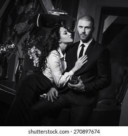 Couple indoors. Sensual brunette seduces handsome businessman. Office romance concept