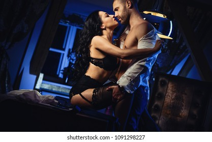 Couple indoors. Two person. Sensual brunette long hair in black lingerie underwear, bra and panties and handsome mature man kissing, having passionate sex in office workplace. Office romance concept