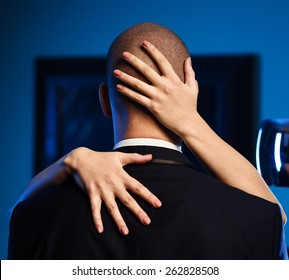 Couple indoors. Woman hugging a man in suit. Woman hands on the mans head. Office romance concept