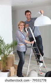 A couple installing a lamp in their new home.